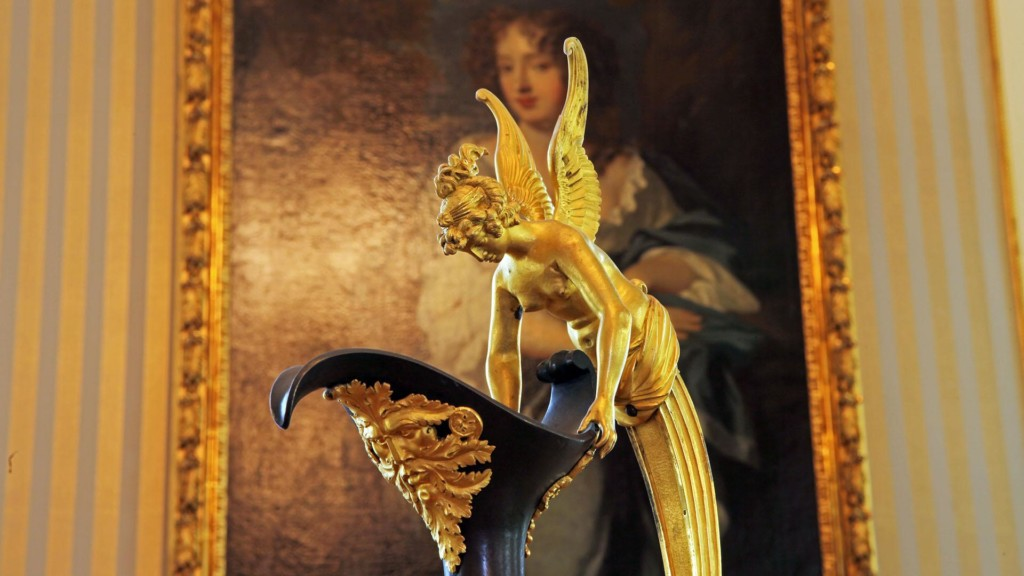 Kuvan etualalla on koristeellinen vanha kannu, jonka kahva on naispuolisen enkelin muotoinen. Enkelin siipien välistä kuvan taustalla hymyilee nainen vanhassa muotokuvamaalauksessa.