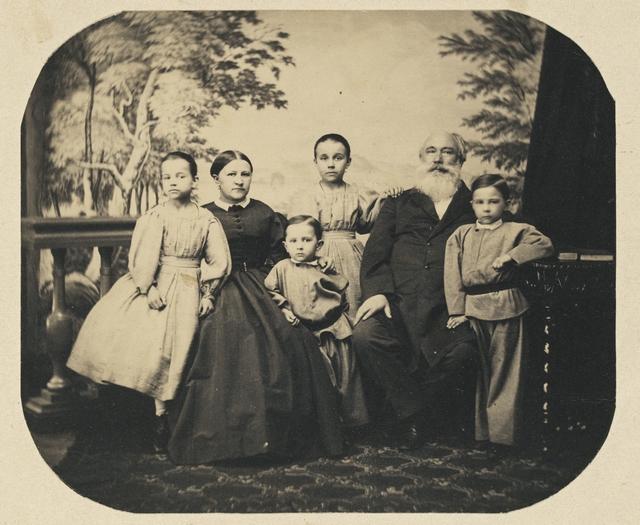 Vanhemmat ja neljä lasta maisemalavasteen edessä.
