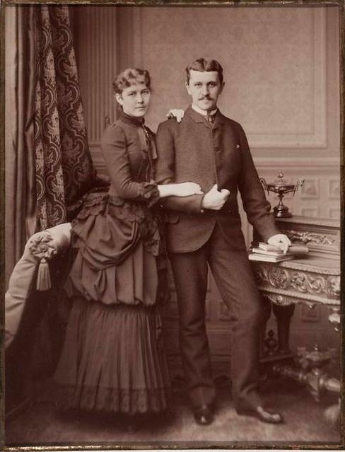 Nuori pari tummissa vaatteissa seisoo salonkilavasteessa ja katsoo suoraan kuvaajaan.
