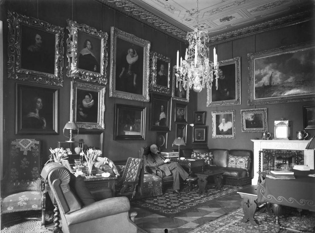 Valkoviiksinen mies istuu huoneessa, jonka seinät ovat täynnä arvotauluja ja katosta roikkuu kristallikruunu.