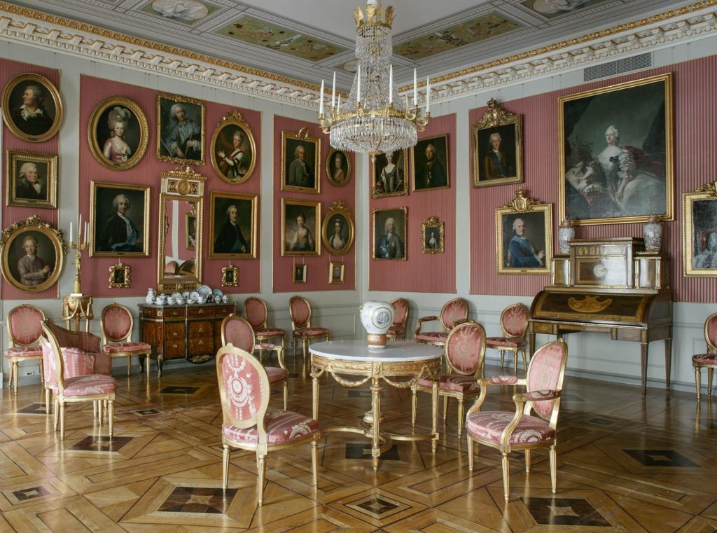 Gustavian furniture in pink room with 18th century portraits.