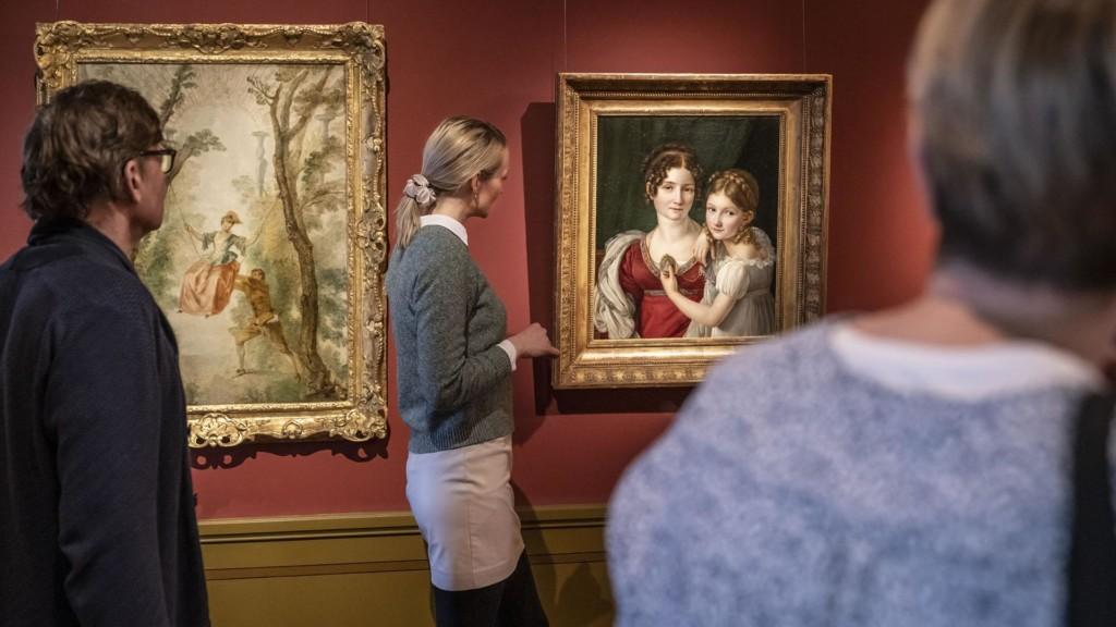 Kolme ihmistä katsoo vanhaa taideteosta, jossa äiti ja lapsi.