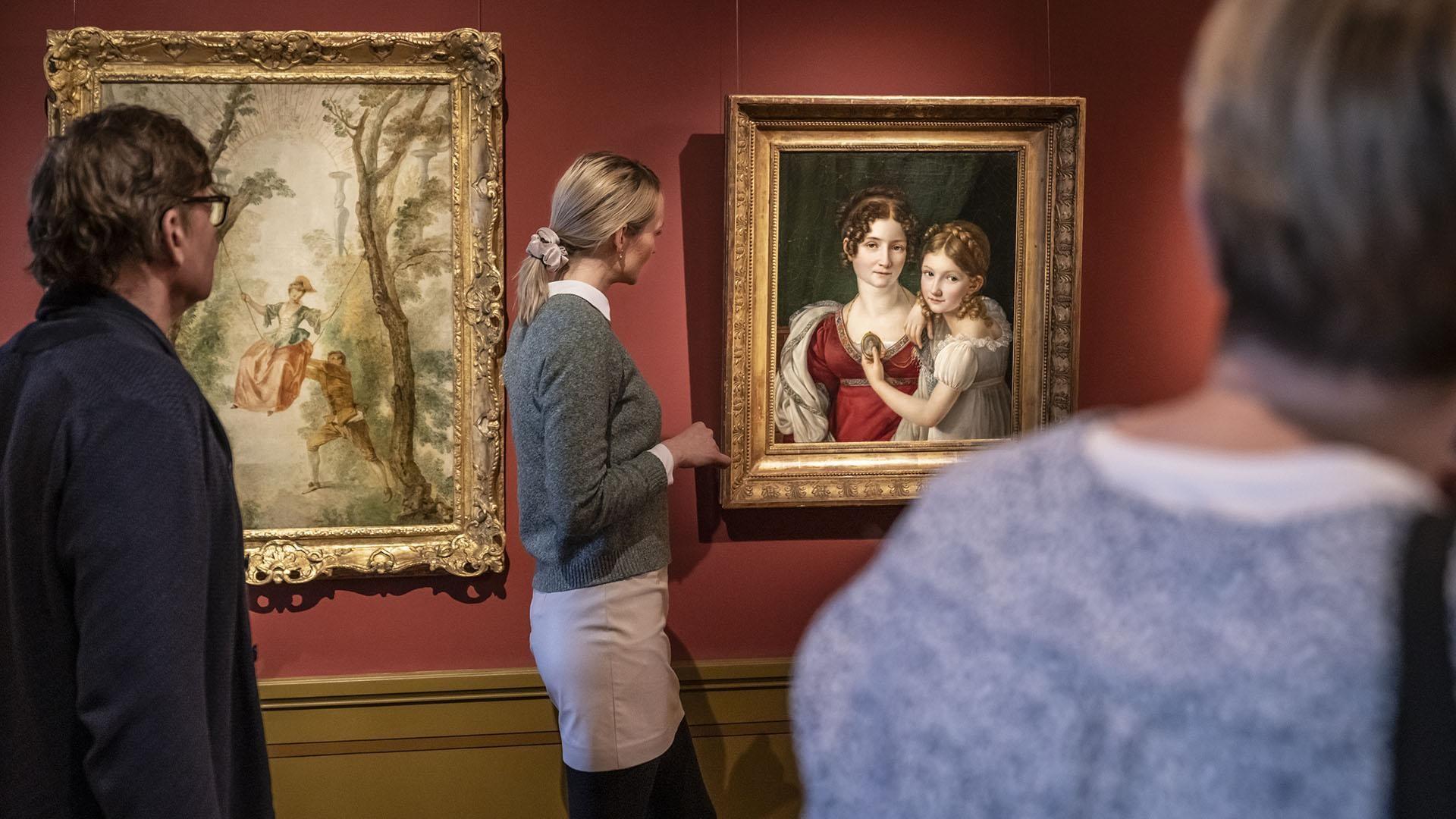 Visitors viewing paintings.