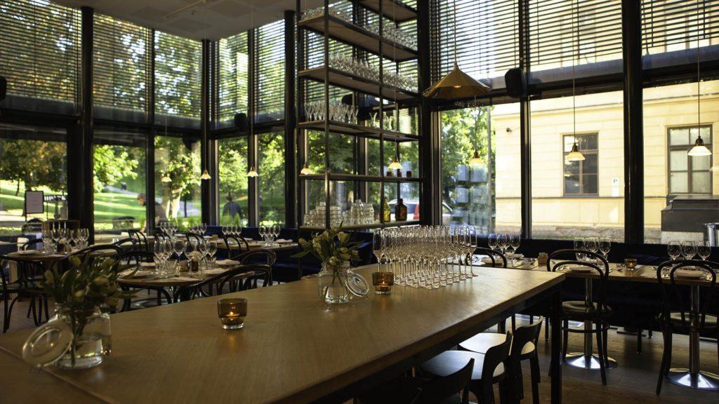 Näkymä ravintolasaliin, jossa katettuja pöytiä ja ikkunasta näkyy vihreä puisto.