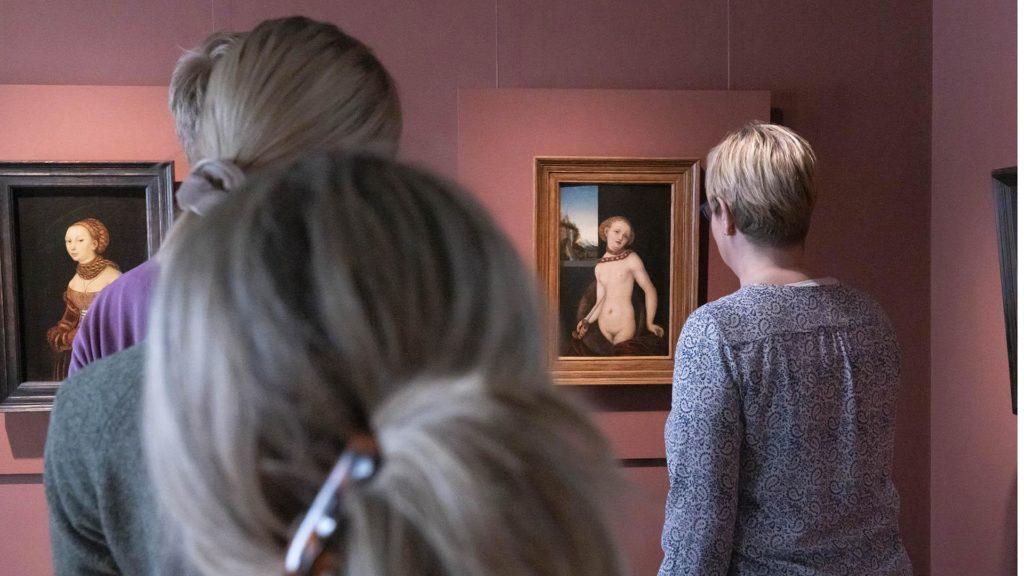 Neljä katsojaa kahden pienen maalauksen edessä.
