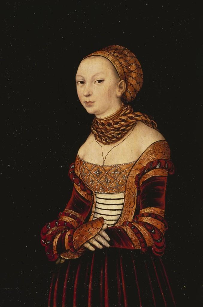 Maalaus naisesta, jolla on yllään punaisesta sametista tehty koristeellinen mekko. Mekko on avokaulainen. Kaulassa hänellä on oranssi huivi ja päässään oranssi koristeellinen myssy.