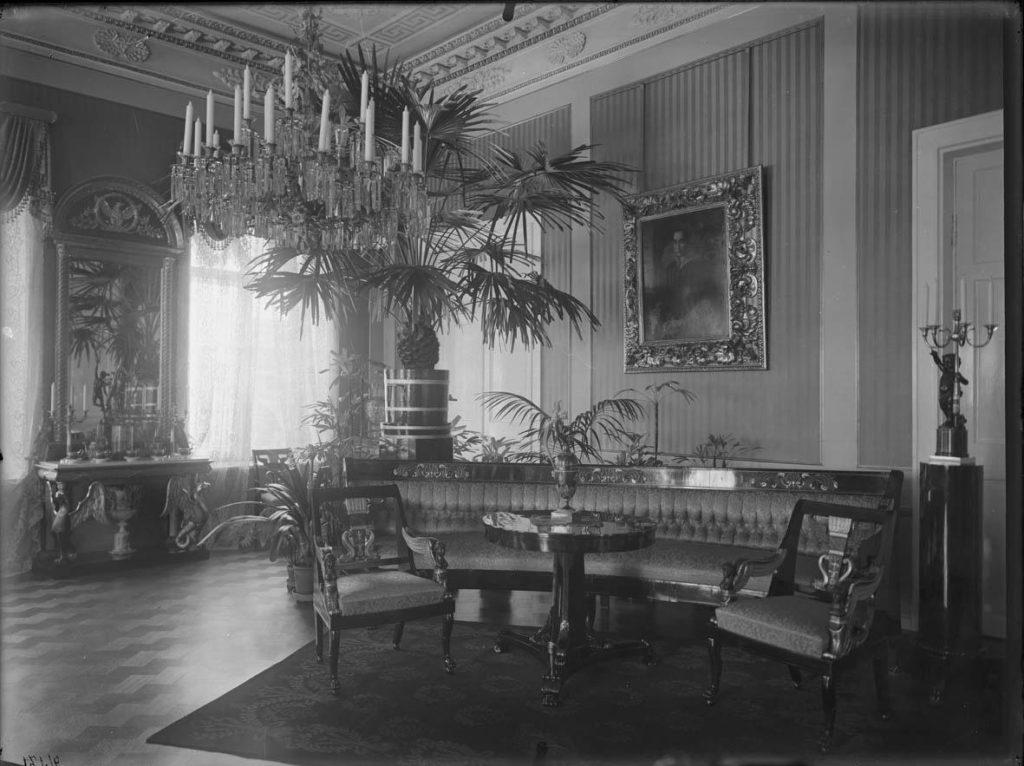 Mustavalkokuva Empiresalista. Etualalla kaksi tuolia, pöytä ja sohva. Takana suurikokoinen palmupuu, muotokuva ja koristeellinen peili.