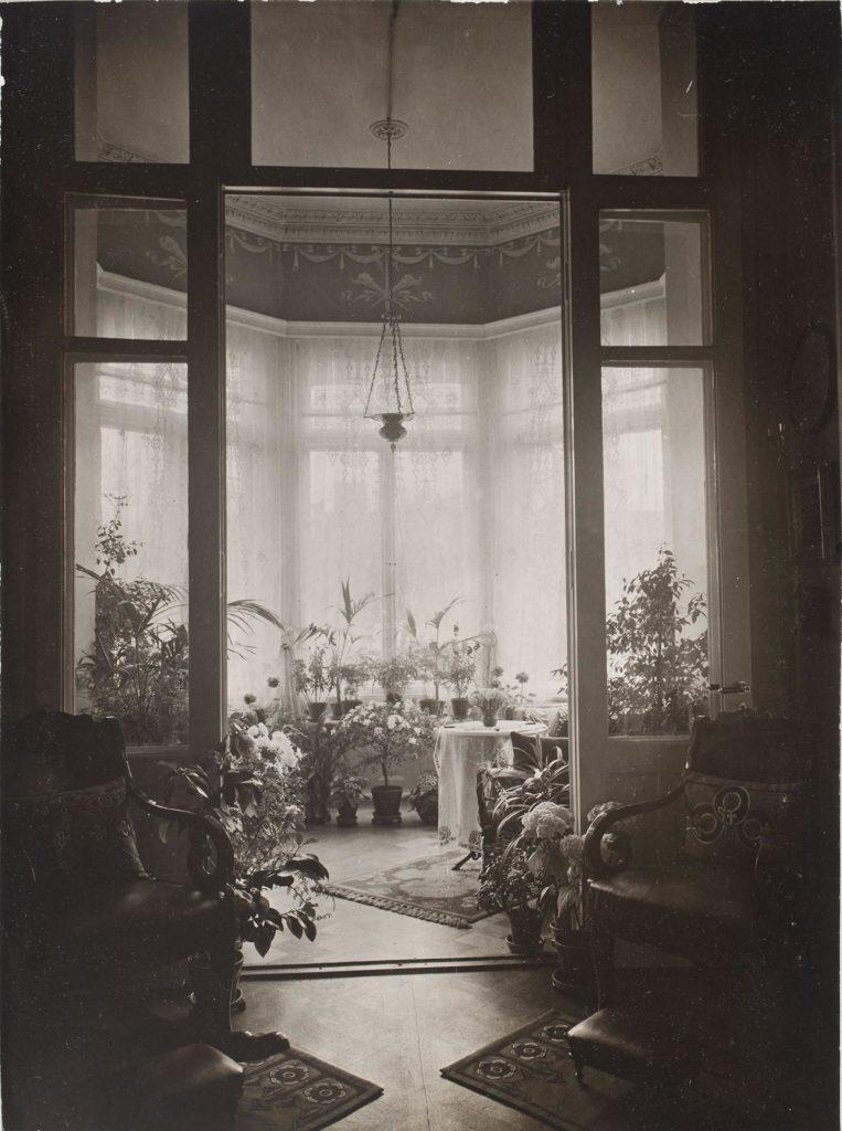 Näkymä erkkeriin, joka on täynnä kasveja. Ikkunoissa pitsiverhot. Etualalla kaksi nojatuolia. Mustavalkokuva.