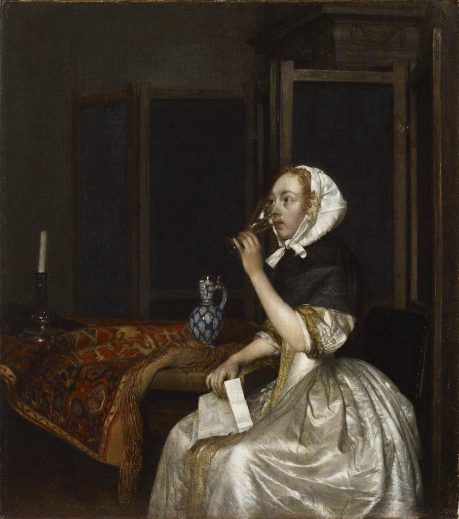Vaaleaan silkkipukuun ja mustaan hartiahuoviin pukeutunut nainen istuu ja juo viiniä. Hänenen hiuksiaan peittää valkoinen kangas. Pöydällä naisen viressä on sininen koristeellinen posliinikannu ja kynttilä.