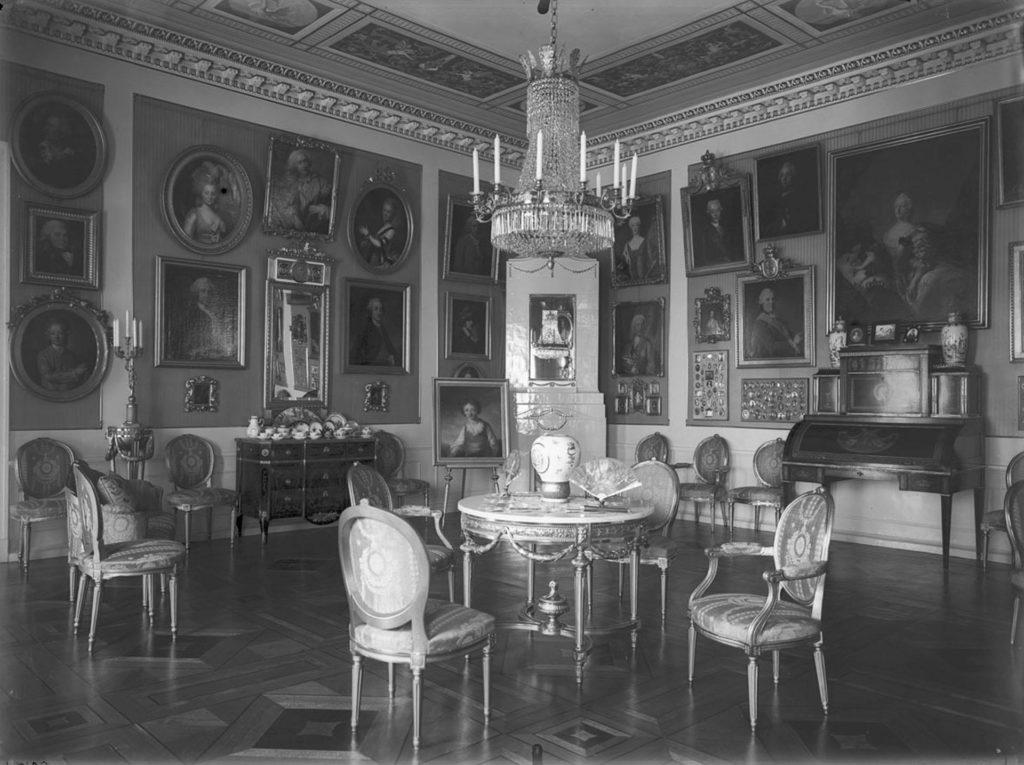 Tuoleja ja pöytä salissa. Pöydän päällä kattokruunu. Huoneen seinät ovat täynnä muotokuvia ja huoneen nurkassa on kakluuni. Mustavalkokuva.