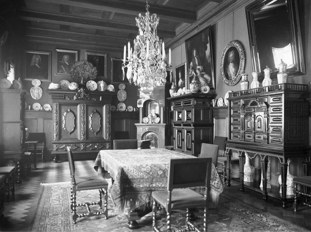 Näkymä huoneeseen, jossa on pöytäliinalla peitetty pöytä. Päydän ympärillä on neljä tuolia ja yllä kattokruunu. Huoneen seinustoilla on massiivisia puisia kaappeja ja seinillä muotokuvia. Mustavalkokuva.