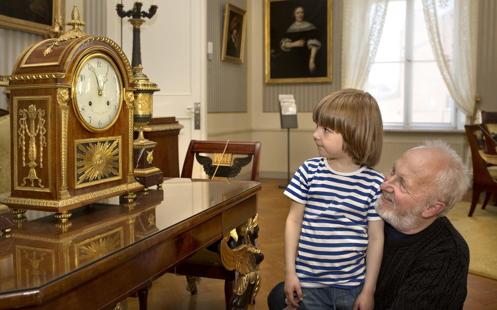 Isoisä ja pikkupoika katselevat koristeellista pöytäkelloa.