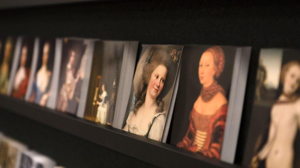 Postikortteja hyllyllä. Korteissa on kuvia vanhojen taideteosten naishahmoista.