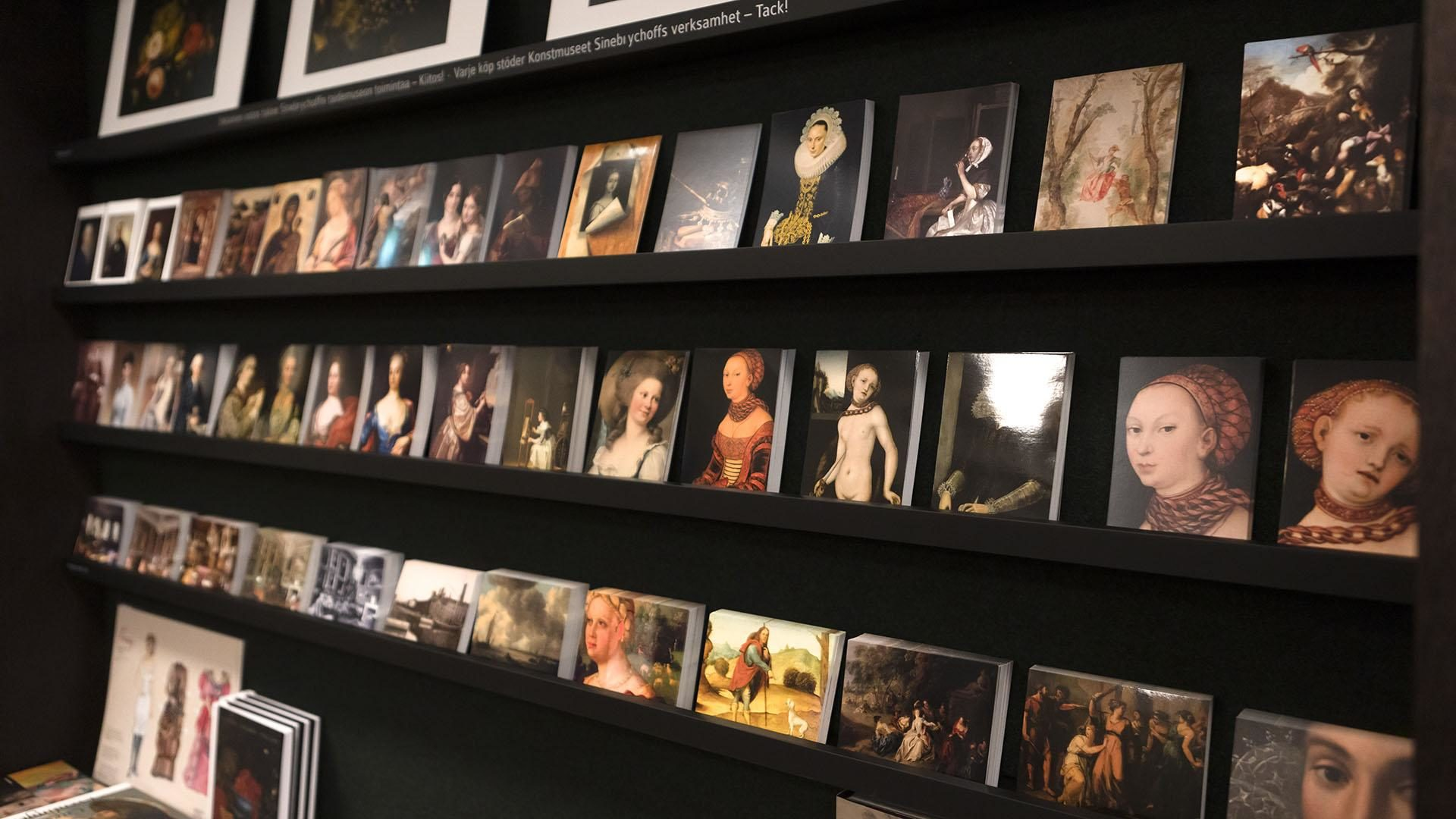 Mustassa hyllyssä Sinebrychoffin taidemuseon teoksista tehtyjä postikortteja. Useimmissa ihmishahmoja.