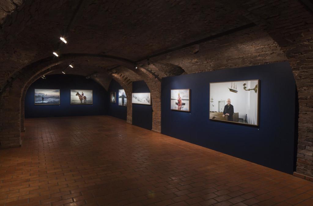 Näyttelysali punatiilikellarissa. Värivalokuvia sinisillä seinäkkeillä.