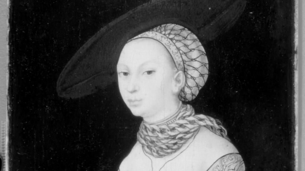 Maalaus. Naisen muotokuva, jota on tutkittu infrapunakameralla. Mustavalkeassa kuvassa näkyy, että naisella on aiemmin ollut leveä lierihattu. Taiteilija on kuitenkin maalannut hatun piiloon lopullisesta työstä.