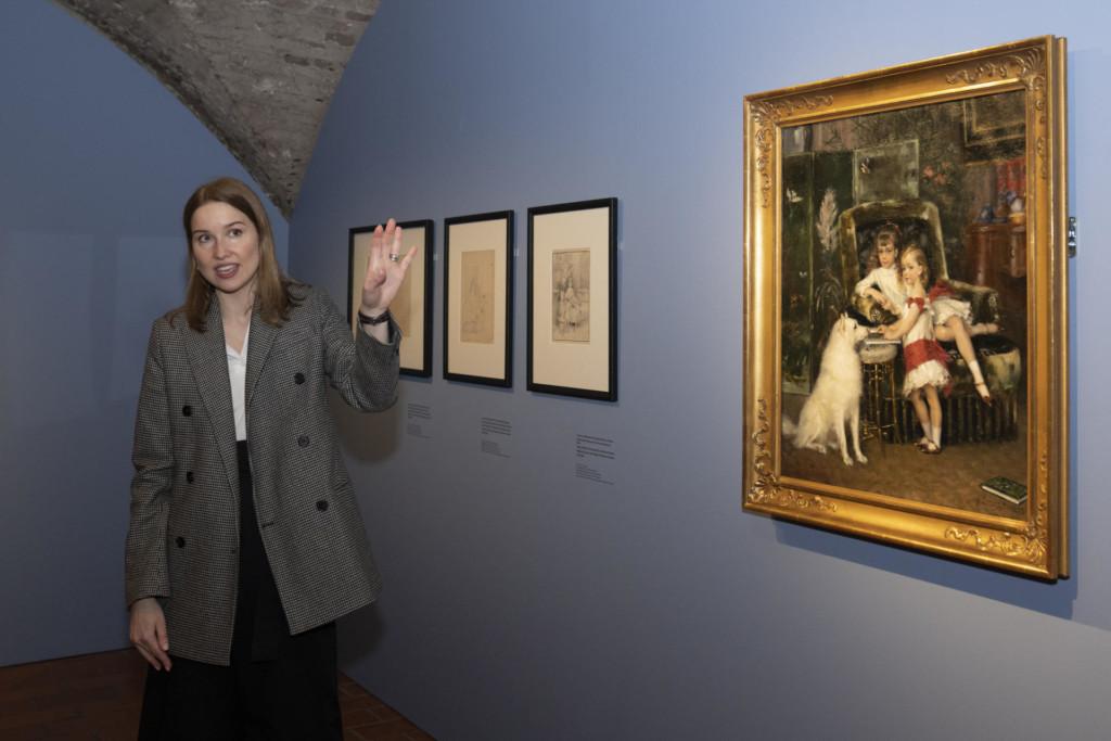 Näyttelynäkymä. Tauluja seinällä. Vasemmalla seisova nainen puhuu yleisölle.