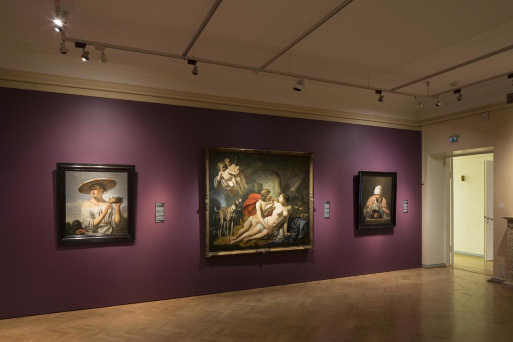 Näyttelysali, josta aukeaa ovi käytävään. Salin violetille seinälle on ripustettu kolme maalausta, joista reunimmaiset ovat naisten potretteja ja keskimmäisessä on mies ja nainen, sekä kaksi enkeliä.