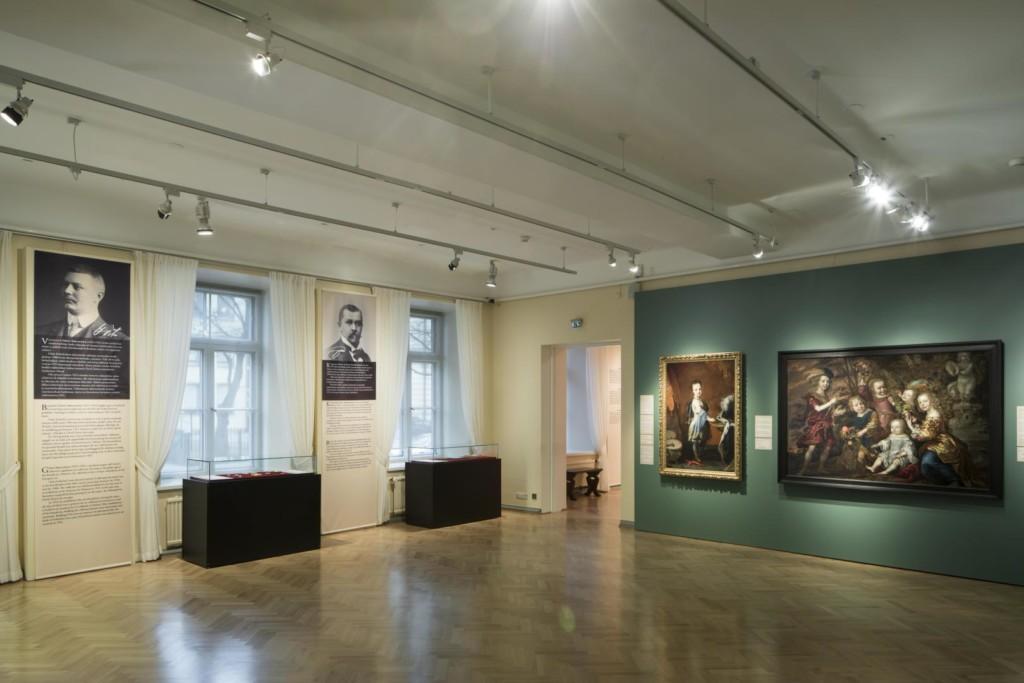 Näyttelysali. Ikkunaseinällä vitriinejä ja tekstipaneeleja. Sivuseinällä muotokuvia.