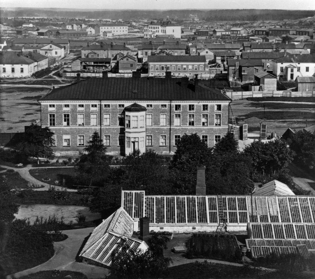 Etualalla on vinokattoisia kasvihuoneita, sekä puisto, jonka takana on Sinebrychoffin talo, jossa taidemuseo nykyään sijaitsee. Talon takana näkyy muita vanhoja rakennuksia. Mustavalkokuva.