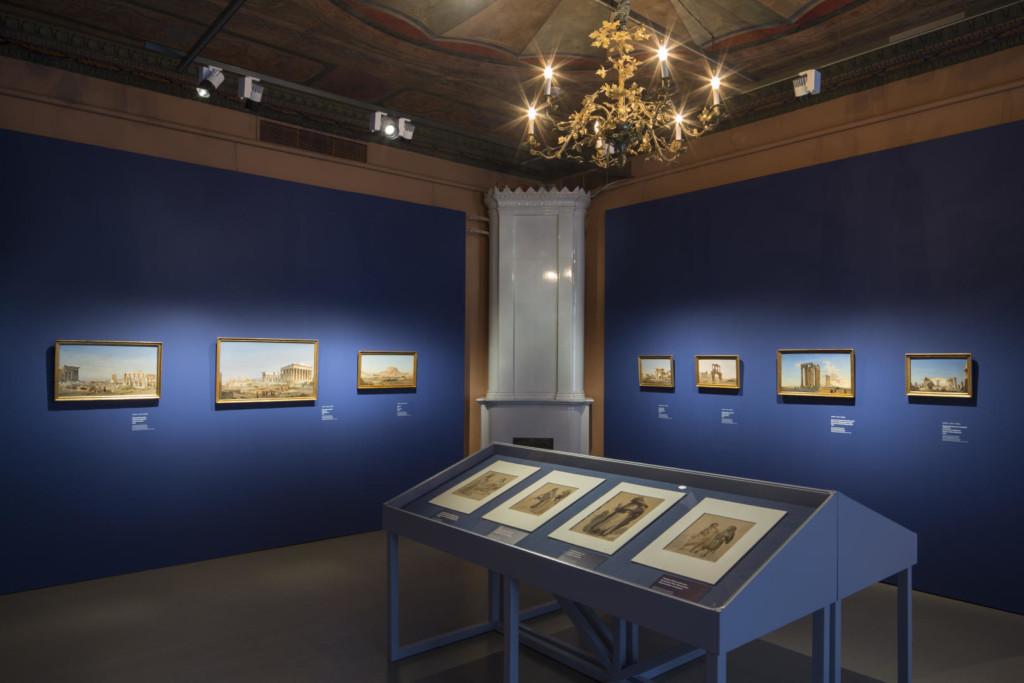 Näyttelysali. Etyalalla vitriinissä piirroksia. Sinisillä seinillä maisemaalauksia.