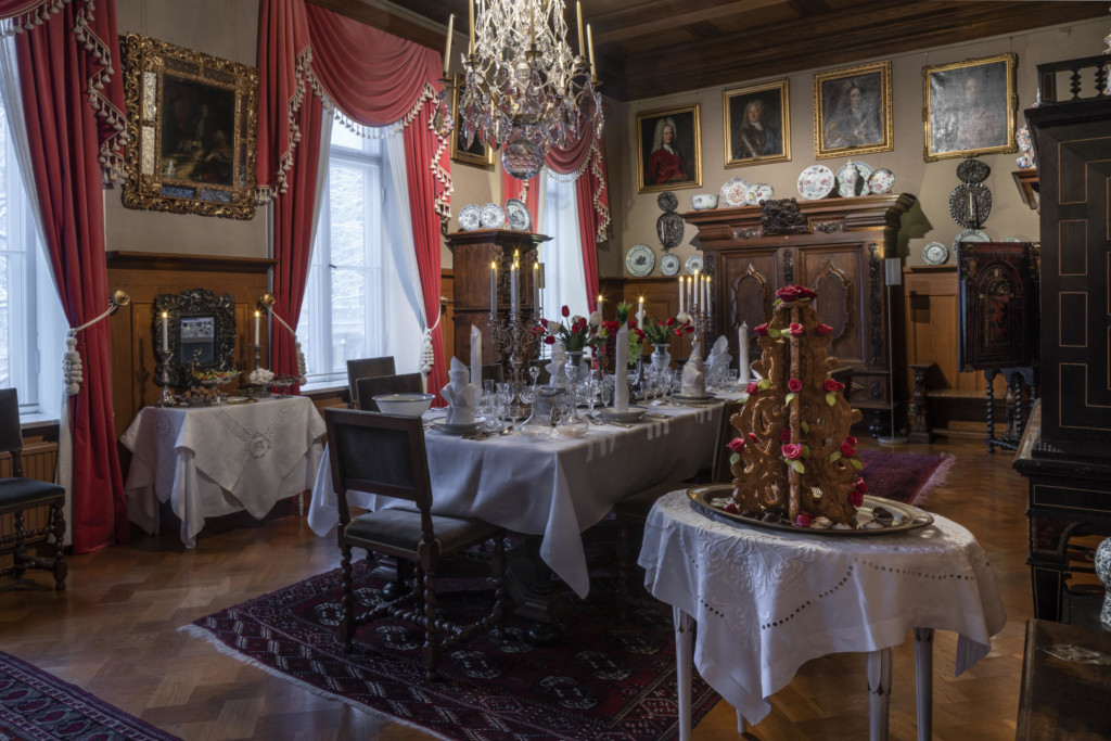 Barokkityylinen ruokasali, jossa kolme valkoisin liinoin katettua pöytää. Etualan pikkupöydällä on suuri krokaani. Seinustan sivupöydällä on pieniä herkkuja. Pitkä ruokapöytä on katettu kahdeksalle.