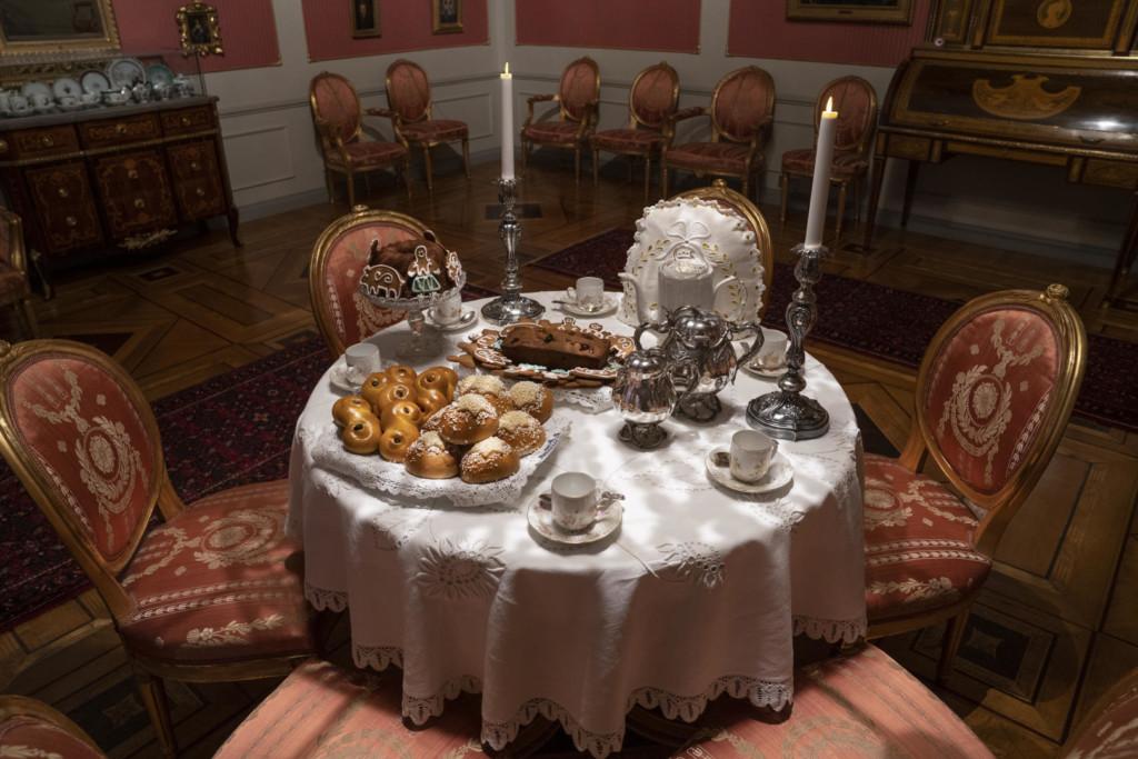 Kahvipöytä kustavilaisessa salissa. Valkoinen reikäkirjailtu pöytäliina pitsireunuksella. Kaksi kakkua, pipareita ja pullia. Kaksi kynttilää. Kahvikattaus neljälle.