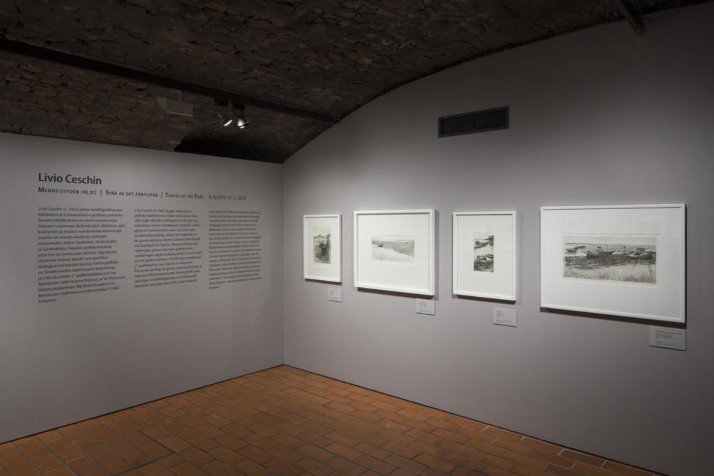 Näyttelysalin nurkka. Toisella seinällä esittelyteksti, toisella neljä taulua.