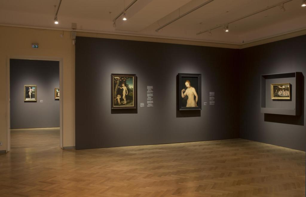 Näyttelysali. Seinillä viisisataavuotiaita puupaneelille tehtyjä maalauksia. Oikealla ilmastokontrolloituun seinävitriiniin ripustettu teos.