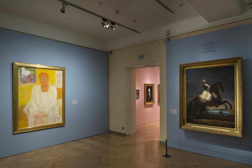 Näyttelynäkymä kahteen saliin. Etualan vaaleansinisillä seinillä hallitsijamuotokuvia eri vuosisadoilta. Oviaukosta näkyy pienempiä muotokuvia vaaleanpunaisella seinällä.