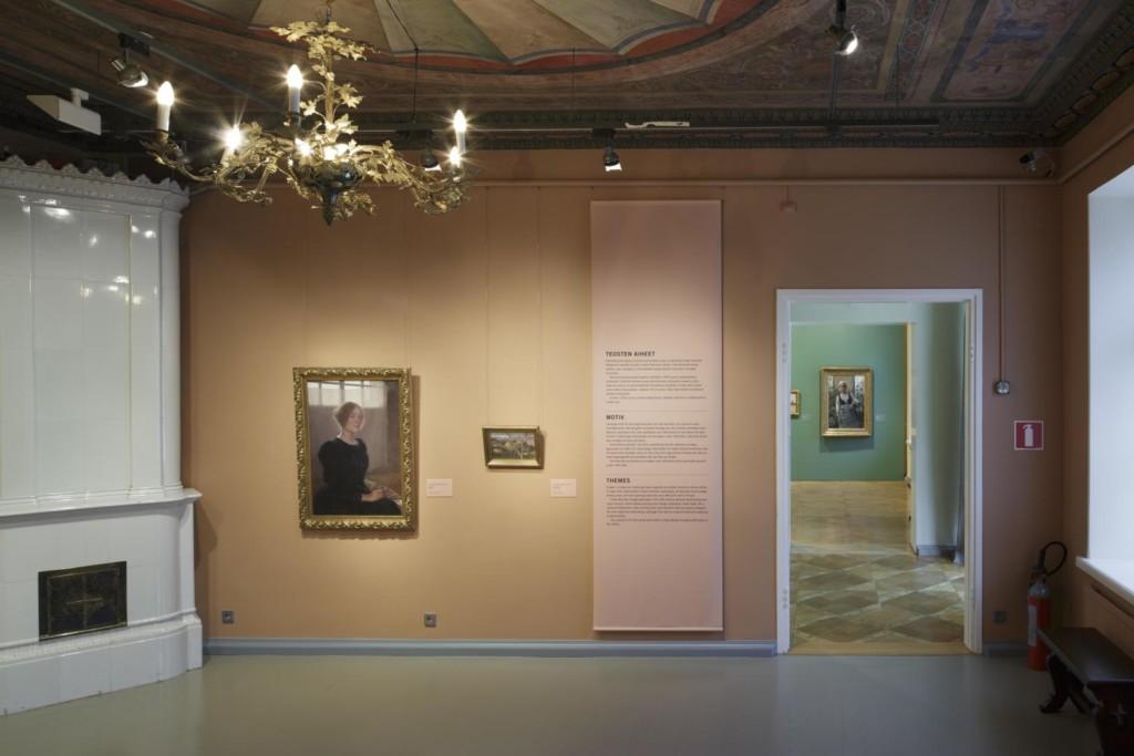 Näyttelysali. Seinällä tauluja ja tekstipaneeli.