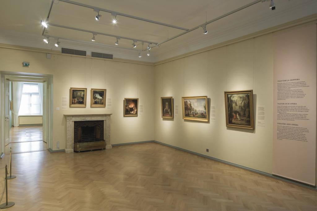 Näyttelysali. Keltaisilla seinillä tauluja ja tekstipaneeli.