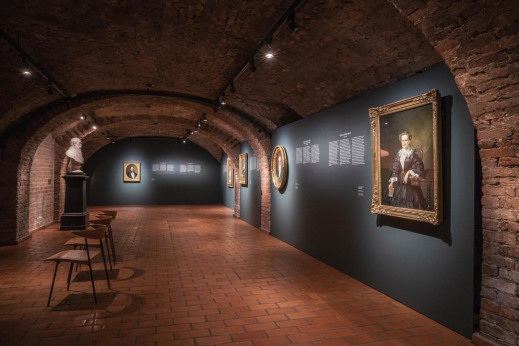 Näyttelynäkymä punatiilikellarista. Seinäkkeillä muotokuvamaalauksia. Jalustalla marmoririntakuva. Salin keskellä tuoleja.