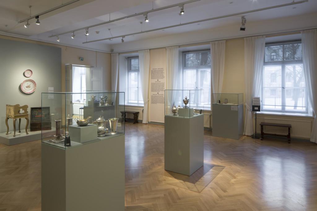 Näyttelysali. Vitriineissä hopeaesineitä. Ikkunaseinällä tekstipaneeli ja penkkejä.