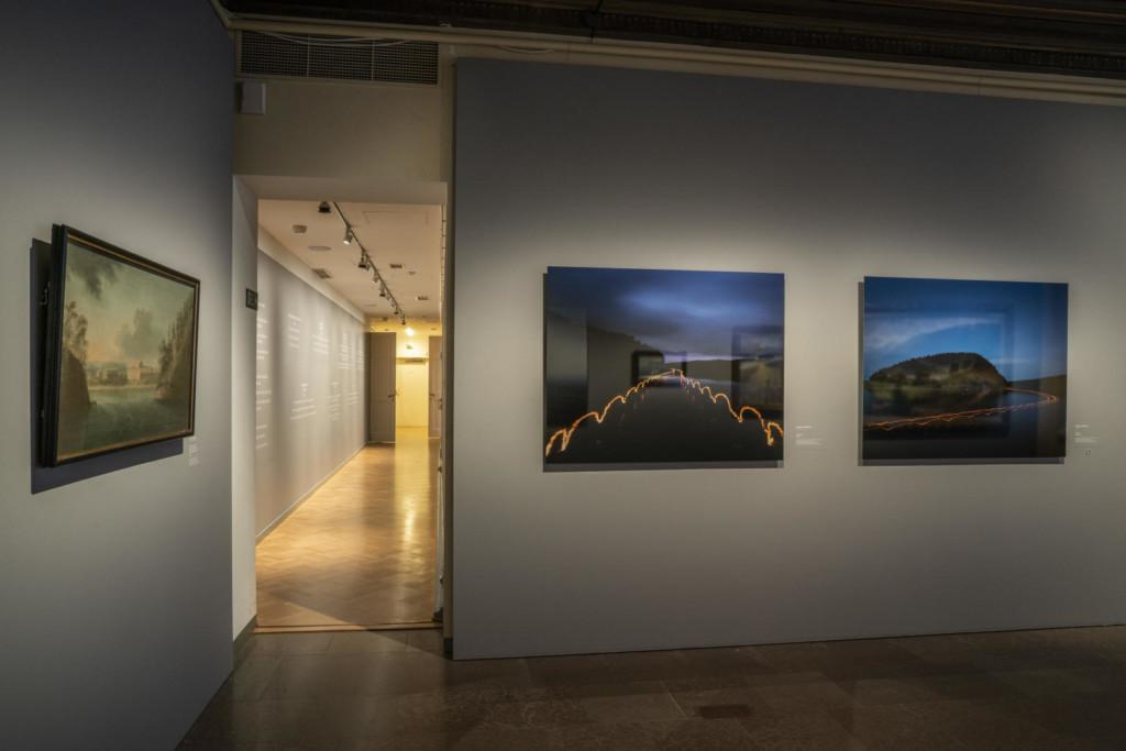 Näyttelysali. Seinillä kaksi öistä järvimaisemaa esittävää valokuvavedosta ja öljymaalaus 1700-luvulta.