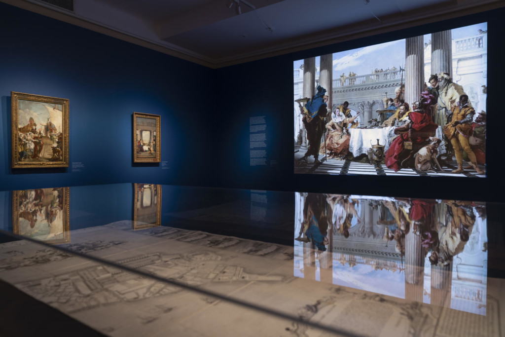 Näyttelysali. Sinisillä seinillä kaksi maalausta ja videoprojisointi. Etualalla vitriinissä Venetsian kartta 1700-luvulta.