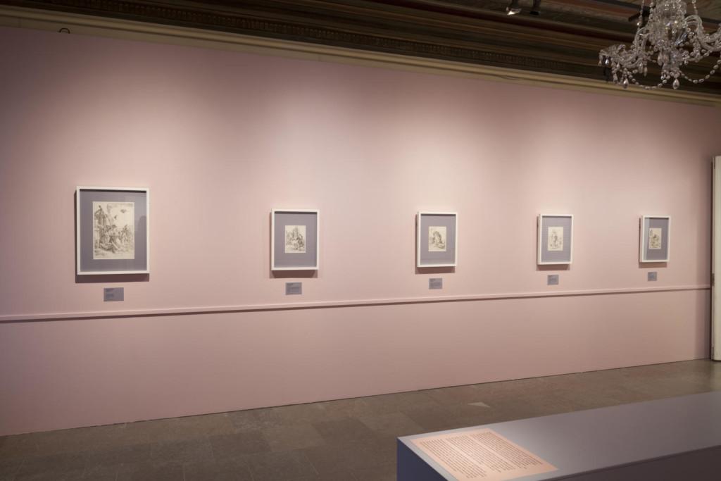 Näyttelysali. Kehystettyjä grafiikanlehtiä vaaleanpunaisella seinällä.