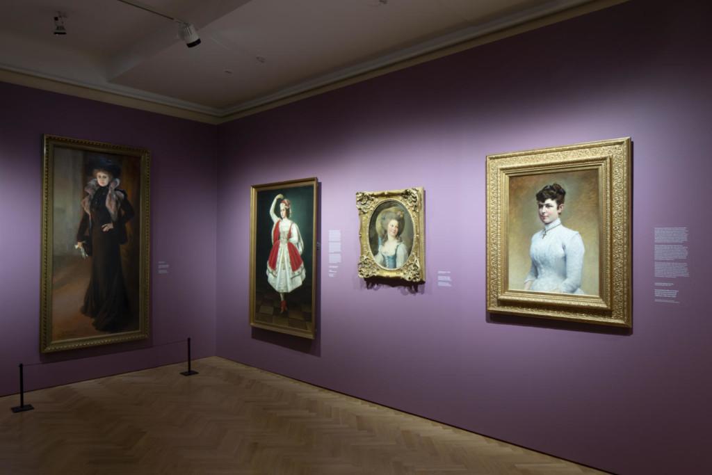 Näyttelysali. Pastellisävyisellä seinällä neljän näyttelijättären muotokuvat.