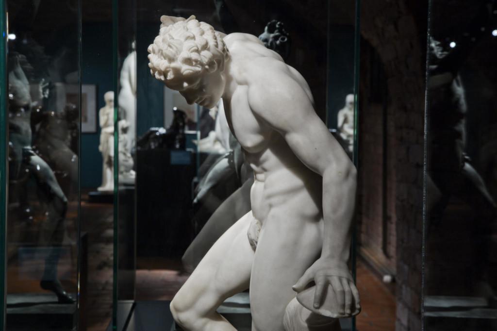 Näkymä näyttelysaliin vitriinilasien läpi. Etualalla marmorista veistetty tanssiva fauni.