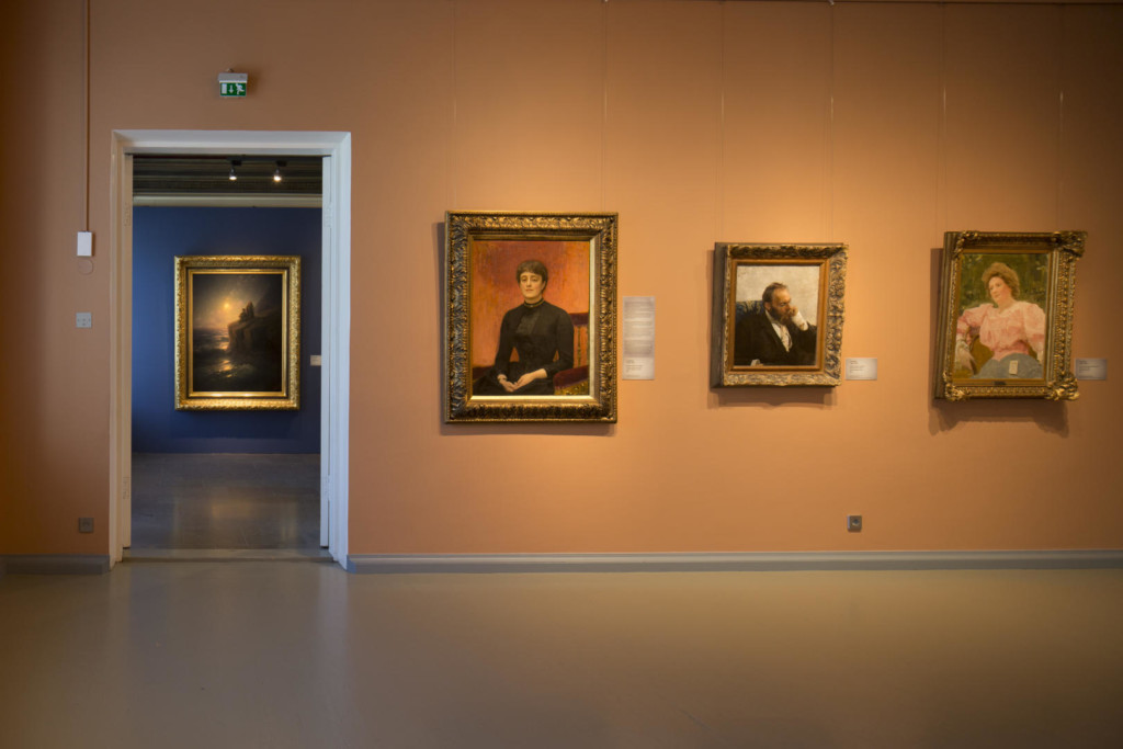 Näyttelynäkymä kahteen saliin. Etualalla muotokuvamaalauksia vaalealla seinällä. Ovesta näkyy merimaisema tummalla seinällä.