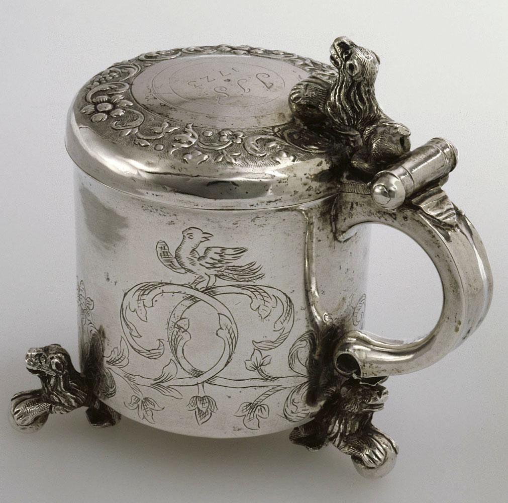 Koristeellinen hopeinen juomakannu, jonka jalat ovat eläinhahmoja, kutan myös kannun sarana. Kannun kyljessä on koristekuvio, jossa on lintuhahmo. Kannun päällä ovat kirjaimet J.J.S ja vuosiluku 1723.