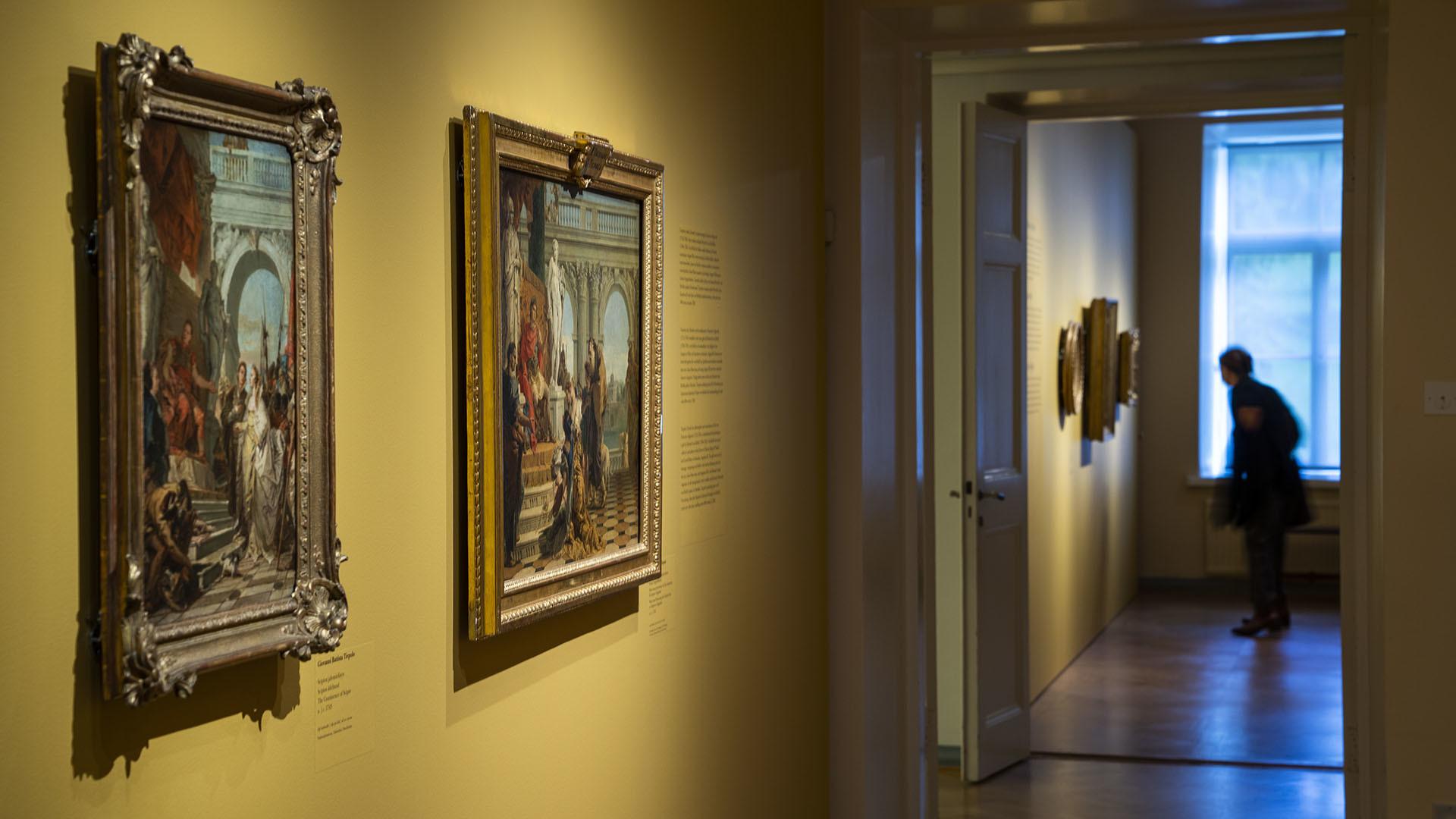 Käytävä, johon on ripustettu maalauksia. Kuvan taka-alalla näyttelyvieras tutkii taulua.