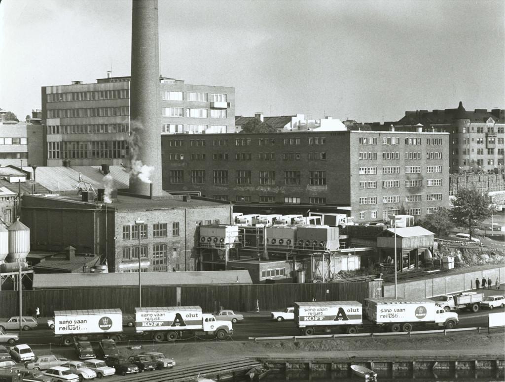 Hietalahden panimoalue rannan suunnasta kuvattuna 6.10.1970. Hietalahdenrantaa ajavat rekat, joissa mainoslauseet: Sano vaan reilusti KOFF!.