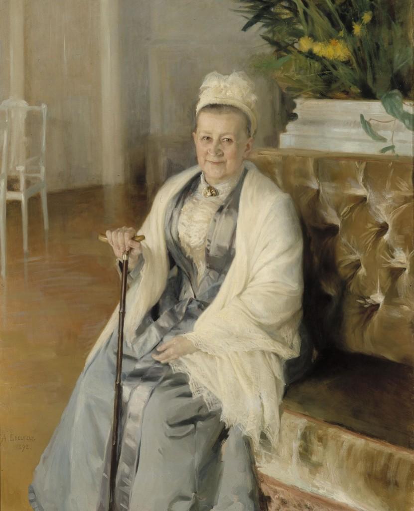 Vanha nainen harmaassa puvussa, harteilla valkoinen shaali ja päässä valkoinen hilkka, istuu keltaisella sohvalla kävelykeppi kädessään.