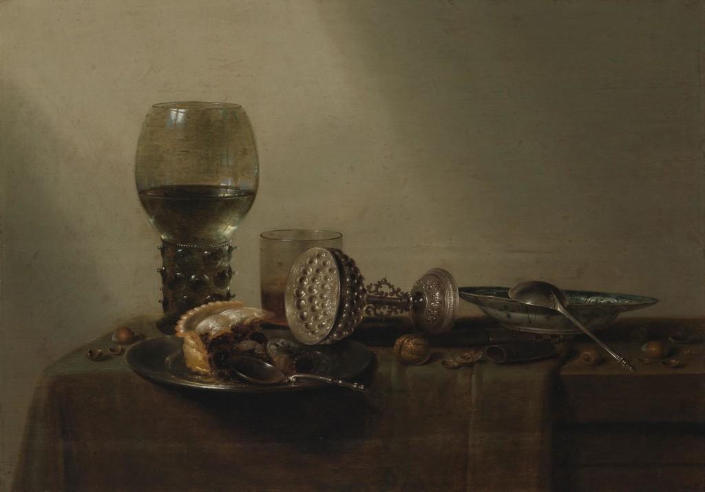 Pöydällä kaksi lasia, kaatunut hopeamalja, veitsi, kaksi lautasta ja lusikkaa, pähkinöitä, pähkinänkuoria ja piirakanpalan rippeet.